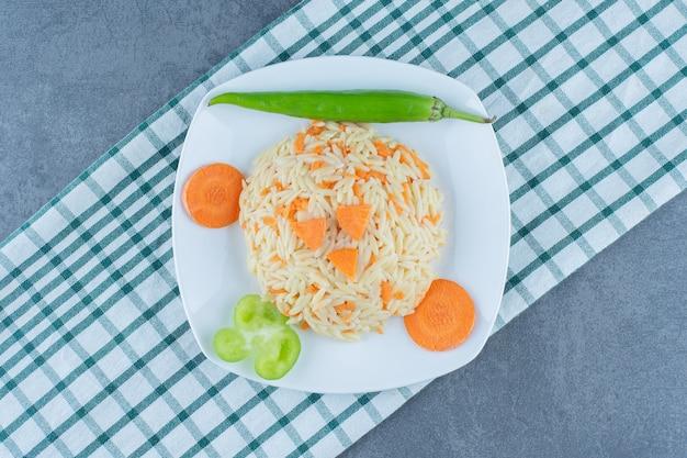 Riso al vapore con carote tritate sul piatto bianco.