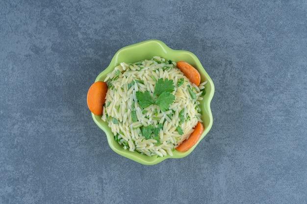 Пропаренный рис с зеленью в зеленой миске.