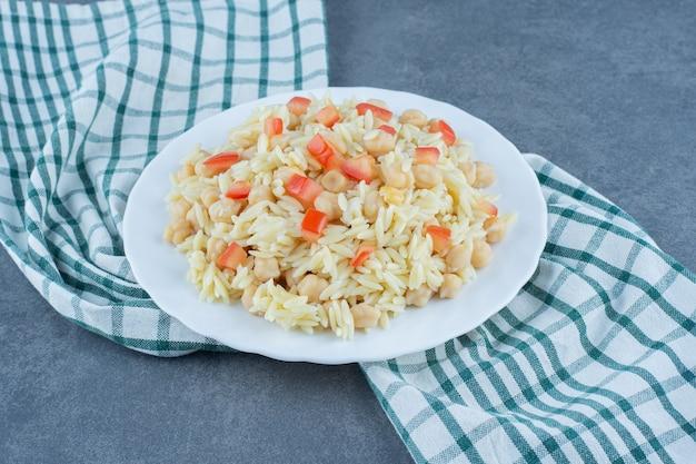 Вареный рис с горохом и ломтиками помидоров на белой тарелке.