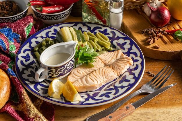 Филе лосося на пару с морковью, кабачками и молодой стручковой фасолью на тарелке с традиционным узбекским орнаментом