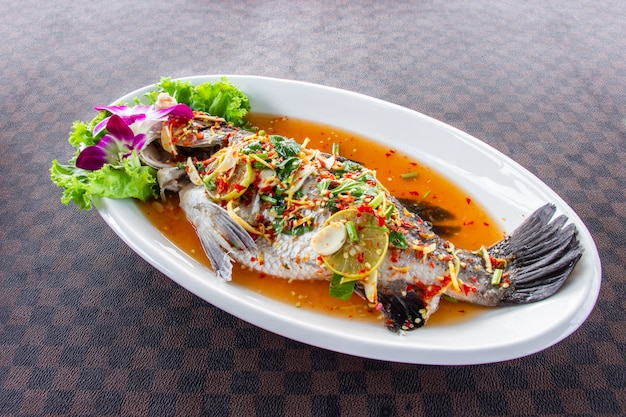 Steamed sea bass fish with lemon put a white ceramic dish on leather floor the grid pattern.