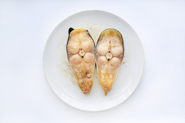 Steamed sliced striped catfish on white plate against white background.