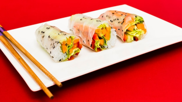 Steamed spring rolls arrange on white plate with chopstick over red surface