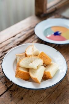 木製のテーブルにカラフルなカスタードを添えた蒸しトーストパン