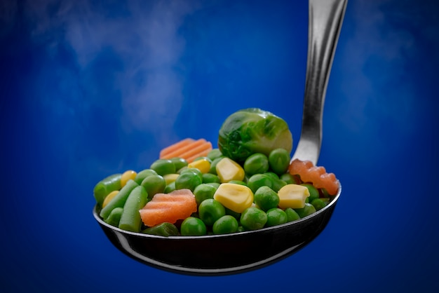 Steamed vegetables in a ladle