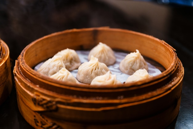 Steamed xiao long bao (soup dumplings) in the bamboo basket. served in restaurant in taipei, taiwan.