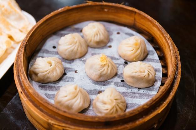 Steamed xiao long bao (soup dumplings) in the bamboo basket.