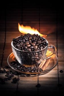 一杯のコーヒー、シナモンスティック、コーヒー豆を火で蒸す