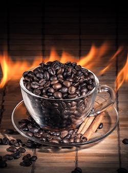 Дымящаяся чашка кофе с палочками корицы и кофейные зерна в огне
