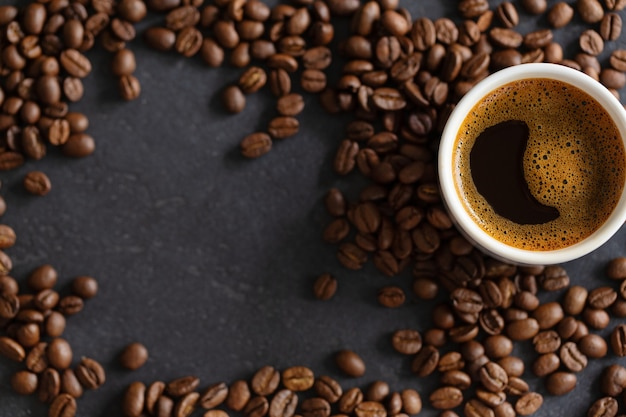 Steaming espresso cup on coffee beans background. closeup