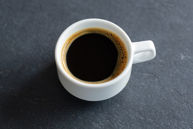 Steaming espresso cup on grey background. closeup