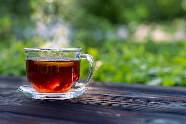 Дымящаяся стеклянная чашка с чаем и лимоном на деревянном столе селективный фокус с короткой глубиной резкости