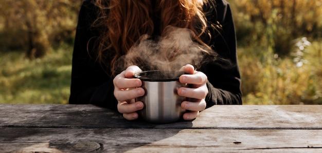 子供の手にお茶のマグカップを蒸します。