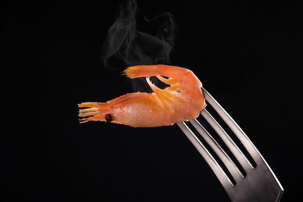 Steaming shrimp on a fork against black background
