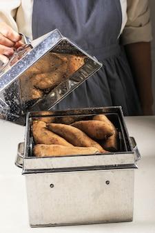Приготовление сладкого картофеля на пару в традиционном паровом котле alumunium. азиатская женщина рука открытая дымящаяся крышка