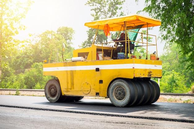 Строительство дорог асфальта с машиной и тележкой steamroller на скоростном шоссе в таиланде.