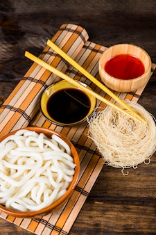 Steams udon noodles; rice vermicelli and sauces with wooden chopsticks over the place mat against wooden table
