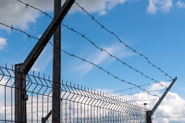 Steel barbed wire on a high iron fence against the background of clouds with blue sky