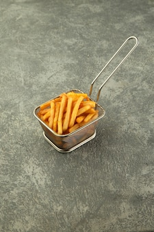 Steel basket of french fries on plain grey background
