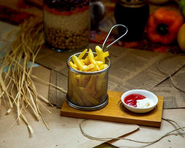 A steel basket of french fries served with ketchup and mayonnaise