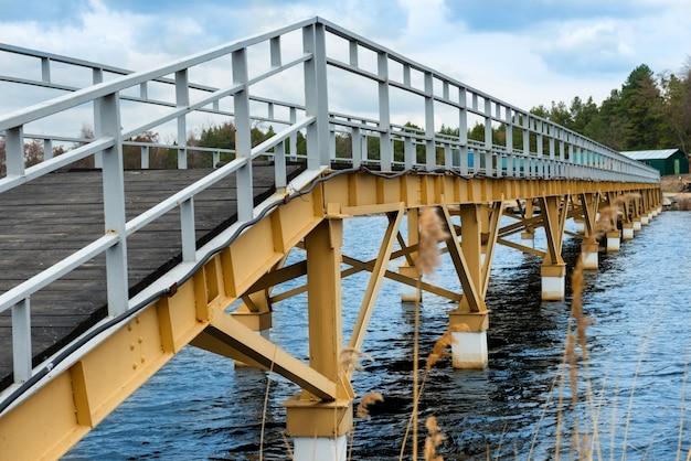 Steel bridge along river bank, blue sky at background
