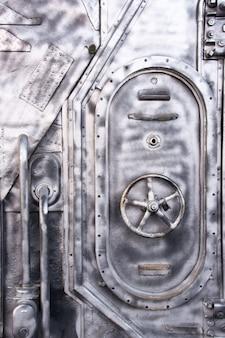 Стальная дверь военного корабля. запертый люк для подводной лодки металлической дверью в конце коридора вмф.