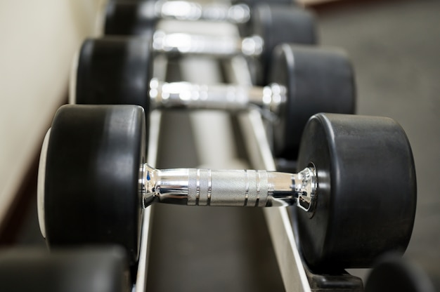 Steel dumbbells placed on the floor at the gym.
