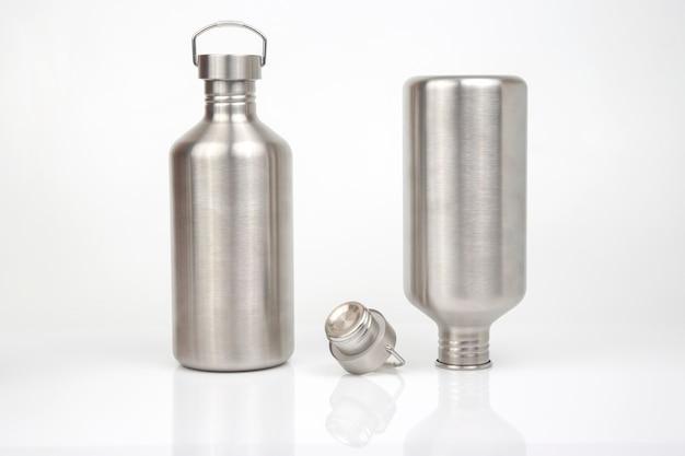 흰색 배경에 물과 음료를 위한 강철 플라스크. 생존 하이킹 장비