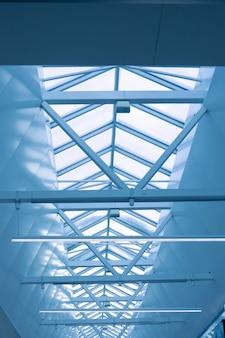 사무실 천장의 유리 지붕의 강철 프레임은 용접으로 연결된 금속 빔으로 만들어집니다.
