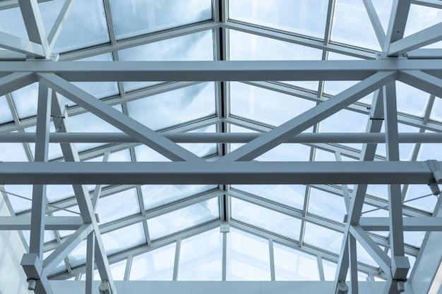 창고 천장의 유리 지붕의 강철 프레임은 용접으로 연결된 금속 빔으로 만들어집니다.