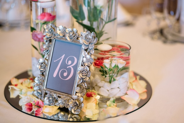 Steel frame with number 13 stands on glass tray with flowers