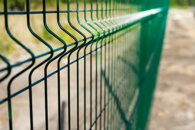 필드의 강철 격자 울타리. 잔디와 금속 울타리 와이어
