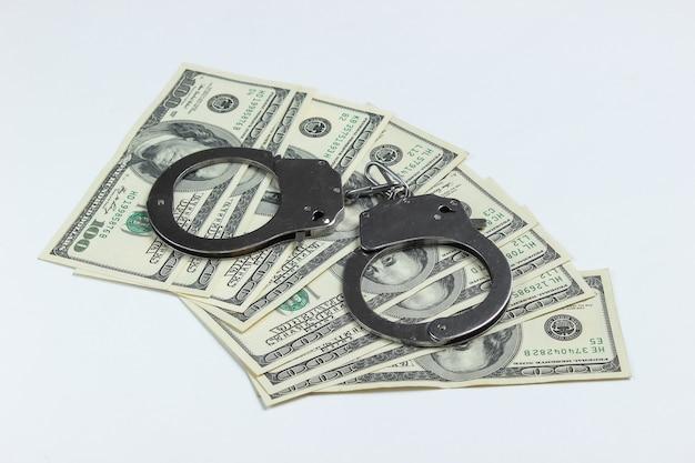 Стальные наручники и стодолларовые банкноты на белом фоне.
