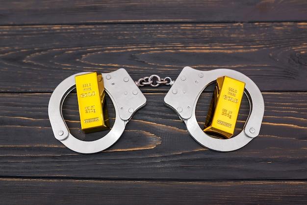 Стальные наручники и два золотых слитка на деревянном фоне. вид сверху.