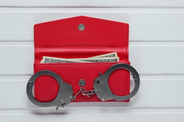 Steel handcuffs with red leather wallet on white table. theft, criminal concept.