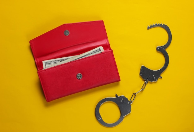 Steel handcuffs with red leather wallet on yellow background. theft, criminal concept.