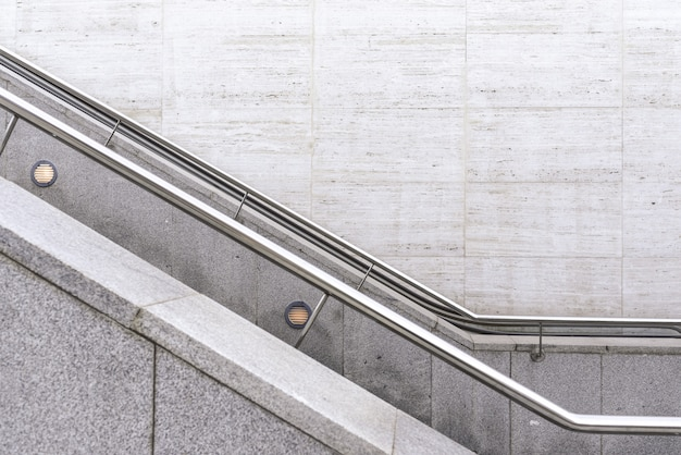 Steel handrails on granite stairs with a wall background.