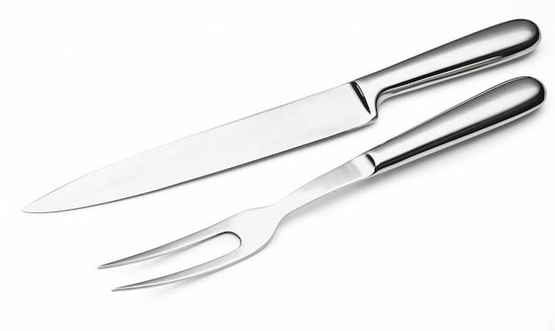 Стальной нож и вилка для резки мяса, изолированные на белом фоне