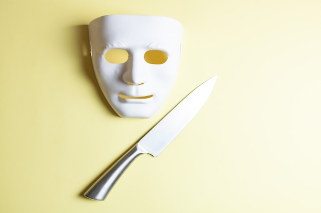 黄色の背景に鋼のナイフとマスク