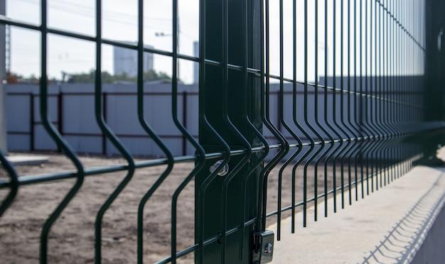 Стальная решетка зеленого цвета забор с проволокой. фехтование. сетка промышленная проволока для забора панелей, металл пвх. монтаж секционного ограждения. забор из сварной сетки. установка сетки для ограждения территории.