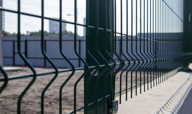 Steel lattice green fence with wire. fencing. grid industrial wire fence panels, pvc metal. installation of sectional fencing. welded mesh fence. installation of a grid for fencing the territory.