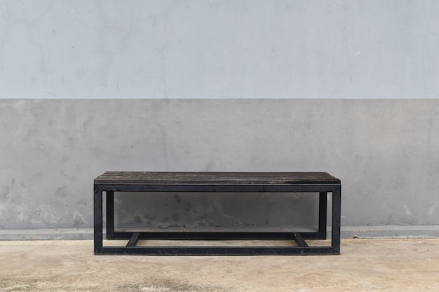 Steel long bench in front of dirty gray old wall