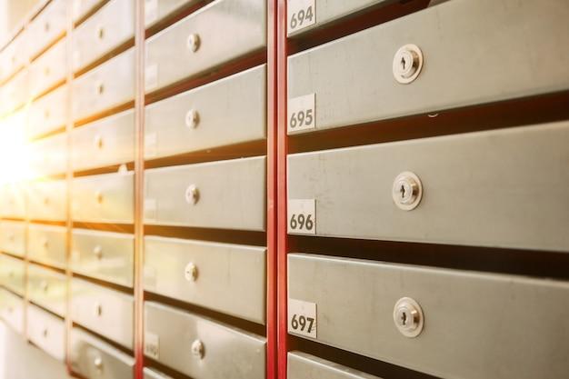 Почтовые ящики стальные в многоквартирном жилом доме. четные ряды пронумерованных почтовых ящиков. концепция переписки в городе. вы можете использовать его в качестве фона для своего объявления. копировать пространство