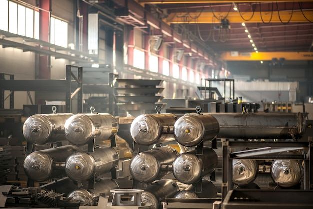 Steel or metal industrial equipment or parts of large machines inside warehouse or factory workshop
