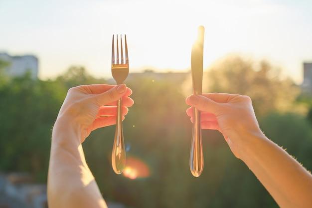 Стальной металлический блестящий нож и вилка в женской руке
