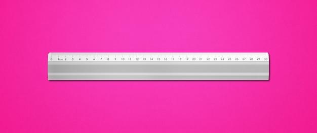 Steel metallic ruler isolated on pink background