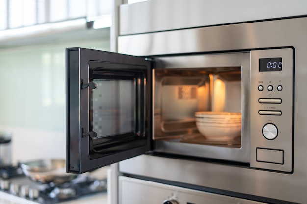 На кухне открыта стальная микроволновая печь.