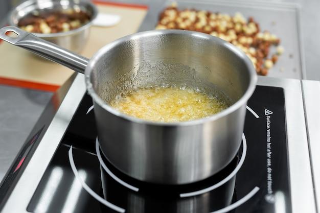 Стальная сковорода с кипящей и пузырящейся сахарной массой для приготовления карамели.