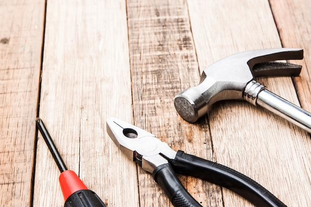 Steel pliers and hammer carpenter tool on wood background
