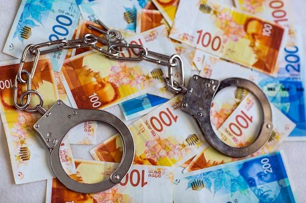 100, 200 nis 지폐가 있는 이스라엘 뉴 셰켈 지폐의 배경에 강철 경찰 수갑